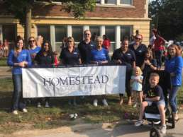 The Homestead Savings team holding a banner that reads,