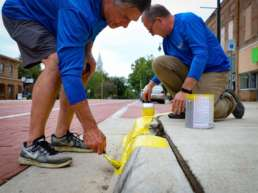 Two Homestead Saving Bank workers bending down to repaint the border of the sidewalk yellow for Community Unity Day.