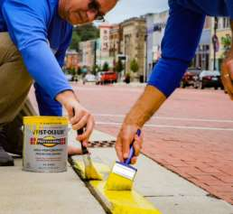 The hands of two Homestead Savings Bank employees as they repaint the border of the sidewalk yellow for Community Unity Day.