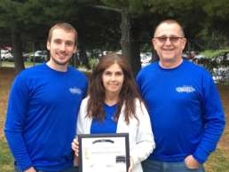 Three members of the Homestead team sanding together in blue Homestead branded shirts. The woman in the center is holding a framed document.