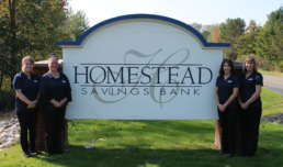 Homestead Savings Bank Leslie team standing in front of their sign
