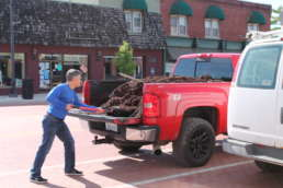 A member of the Homestead team shoveling mulch out of the bed of a red truck.