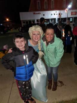A mother and son posting next to a woman dresses as Elsa from Disney's Frozen.