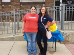Homestead Savings Bank worker and friend smiling in front of a booth at the Springport Summer Festival