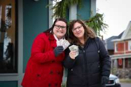 Two women in winter coats fanning five dollar bills for shoppers in downtown Albion.