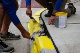 The hands of two Homestead Savings Bank employees as they repains the border of the sidewalk yellow for Community Unity Day.