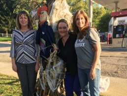 Homestead Savings Bank workers posing next to a scarecrow posted up an a lamppost in Leslie, Michigan.