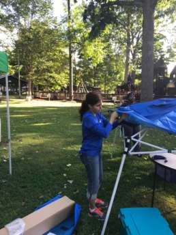 A Homestead Savings Bank employee setting up pop-up tents for guests at the Leslie Fall Festival event.